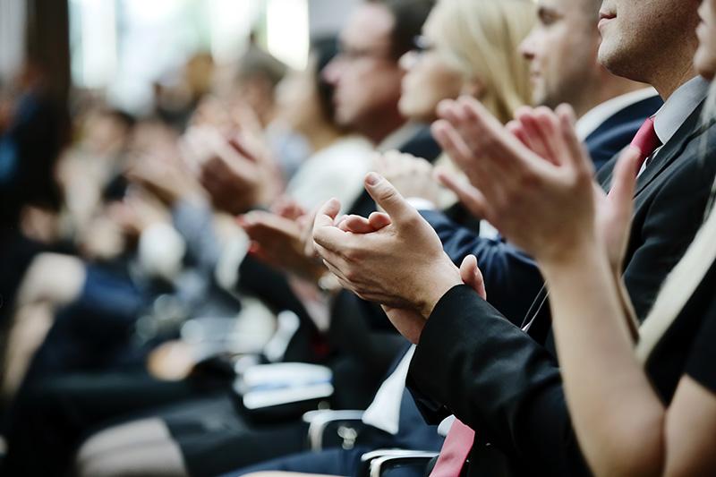 Zuhörer applaudieren beim Knigge Vortrag